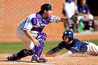 Catcher Josh Spano #21 of the High Point Panthers waits for the throw as Ian Hundley #9 of the Dayton Flyers slides head first across home plate at Willard Stadium on February 26, 2012 in High Point, North Carolina.    (Brian Westerholt / Four Seam Images)