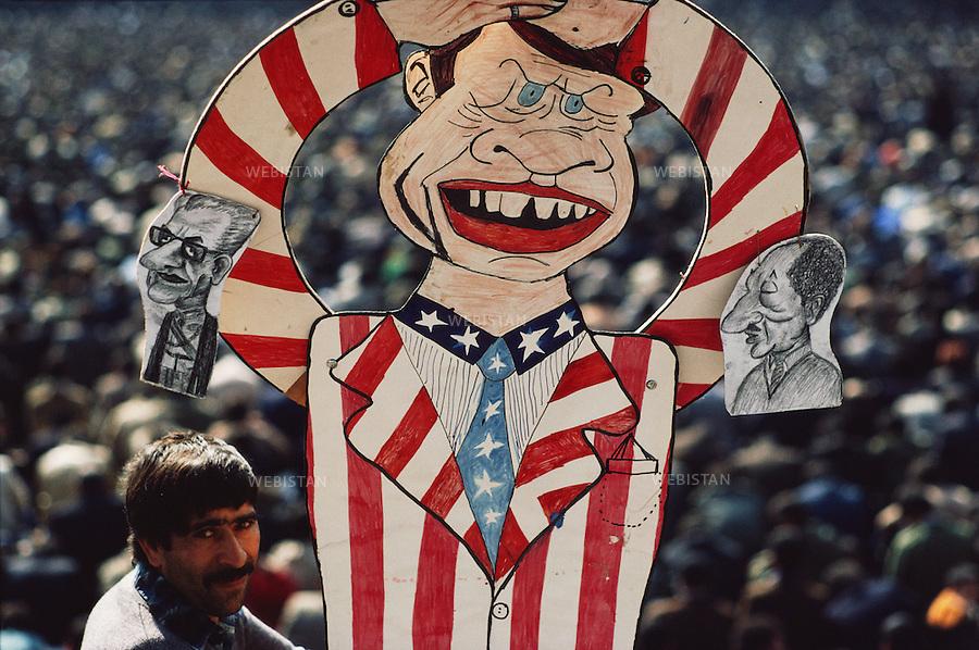 TEHRAN, IRAN - 1979: A man holding a caricature of Jimmy Carter, the U.S. president at that time, during the Friday prayer at Tehran University. (Photo by Reza/Webistan)<br /> T&eacute;h&eacute;ran, Iran - 1979 : Un homme tient une caricature de Jimmy Carter, pr&eacute;sident des Etats Unis , pendant la pri&egrave;re du vendredi, &agrave; l'universit&eacute; de T&eacute;h&eacute;ran.