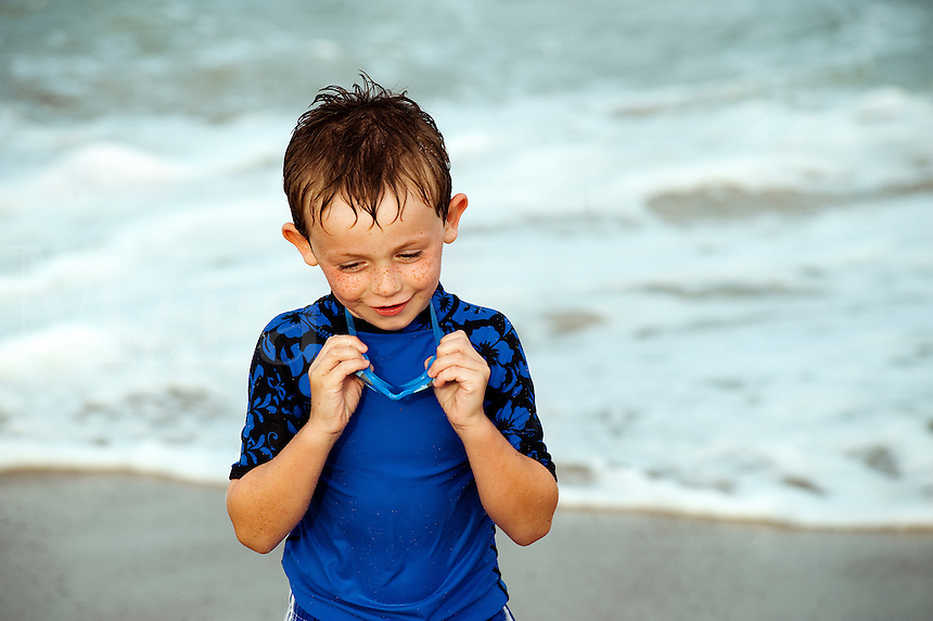 Young boy with goggles enjoys the ocean water.