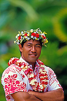 Samoan man in aloha shirt with leis against a background of muted foliage.