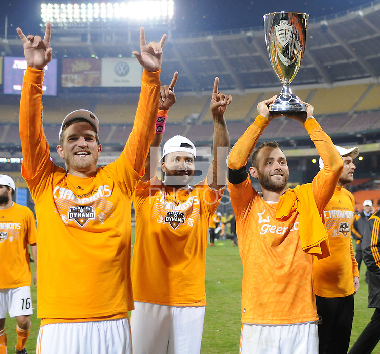 Houston Dynamo captain Brad Davis lifts the Eastern Conference Trophy and salutes the fans along with teammate Jermaine Taylor (middle) and Bobby Boswell (left). D.C. United tied The Houston Dynamo 1-1 but lost in the overall score 4-2 in the second leg of the Eastern Conference Championship at RFK Stadium, Sunday November 18, 2012.