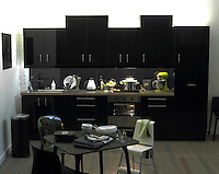 This glamorous black lacquer kitchen with stainless steel work surface is teamed with a small black table and assorted black and white chairs