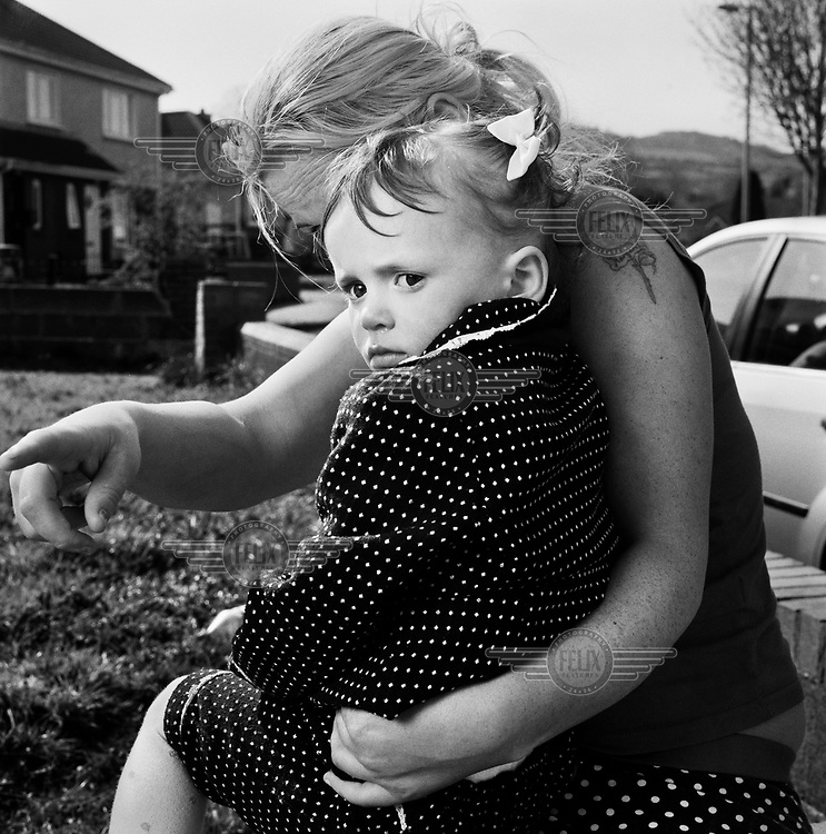 A young girl sits on her mother's knee outside her house on the Jobstown Estate.