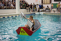 """Vera Linani, a freshman, center, pilots her team's boat in the Brooklyn Technical High School Cardboard Boat Regatta in the school's pool in Brooklyn in New York on Friday, March 1, 2013. As part of Engineering Week the teams of students constructed boats made only of cardboard and duct tape. The team's assigned """"captain"""" piloted their boat from one end of the pool to the other and back in a heat with other boats, hopefully without sinking. The surviving boats were timed and the winners received bragging rights with an award also going to the most spectacular sinking. (© Richard B. Levine)"""