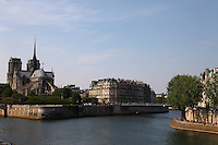 A view of the back of the church of Notre Dame in the Île de la Cité in Paris, with the bridge connecting this isle to the Île de Saint Louis, and a part of the bank on the Seine river of this last one in foreground. There are a lot of tourists. Digitally Improved Photo.