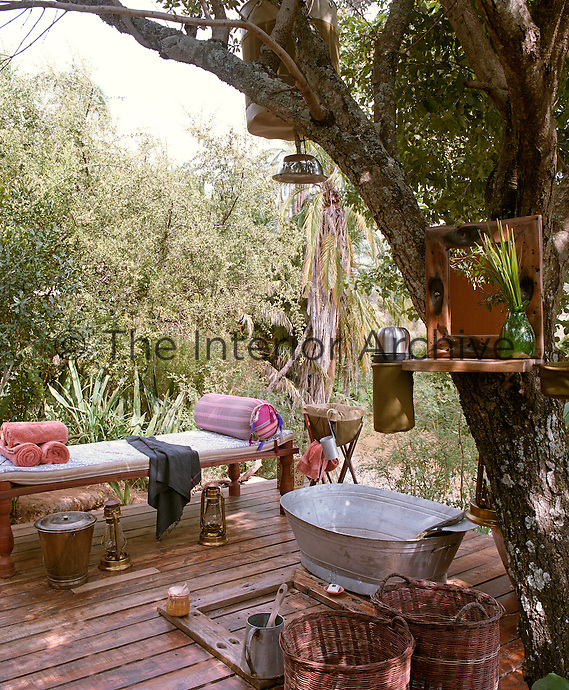 A shower head and a container of hot water are suspended from a tree above a wooden decking in this outdoor bathroom