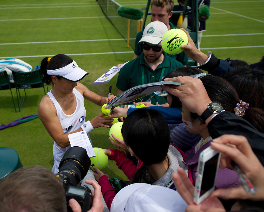 Kimiko Date-Krumm (JPN) isigns autographs after her victory over Alexandra Cadantu (ROU) in their Ladies' Singles Second Round match today - Kimiko Date-Krumm (JPN) def Alexandra Cadantu (ROU) 6-4 7-5<br /> <br />  (Photo by Stephen White/CameraSport) <br /> <br /> Tennis - Wimbledon Lawn Tennis Championships - Day 4 Thursday 27th June 2013 -  All England Lawn Tennis and Croquet Club - Wimbledon - London - England<br /> <br /> &copy; CameraSport - 43 Linden Ave. Countesthorpe. Leicester. England. LE8 5PG - Tel: +44 (0) 116 277 4147 - admin@camerasport.com - www.camerasport.com.