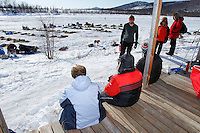 Tourists, flown in for the day, watch teams from the porch of the musher cabin at the ghost-town checkpoint of Iditarod during the 2011 Iditarod race..