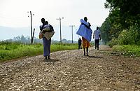 ETHIOPIA, Gambela, people walk long distances to the catholic hospital in Abobo, left Saudi Star Agricultural Development PLC farm land , Saudi Star is owned by Saudi-Ethiopian billionaire Sheikh Mohamed al-Amoudi / AETHIOPIEN, Gambela, die aethiopische Regierung verpachtet grosse Landflaechen an Investoren fuer den Anbau von Nahrungsmitteln fuer den Export, Umsiedlung der lokalen Bevoelkerung fuehrt zu Konflikten, links Ackerflaechen des Investors Saudi-Star, , war ehemals eine Staatsfarm in der Derg Zeit unter Mengistu Haile Mariam , angelegt mit sowjetischer Entwicklungshilfe, Frauen mit Babies auf dem Fussweg zum katholischen Hospital in Ababo