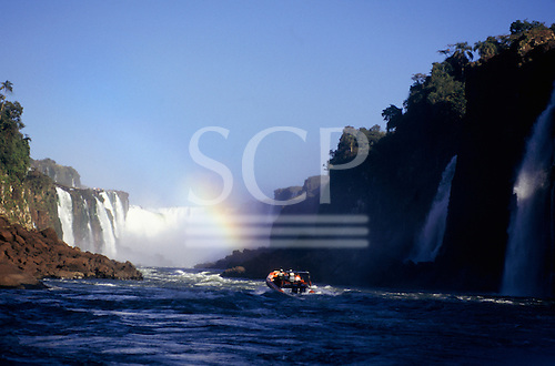 Iguassu Falls, Brazil. Tourist inflatable boat approaching the falls with rainbow.