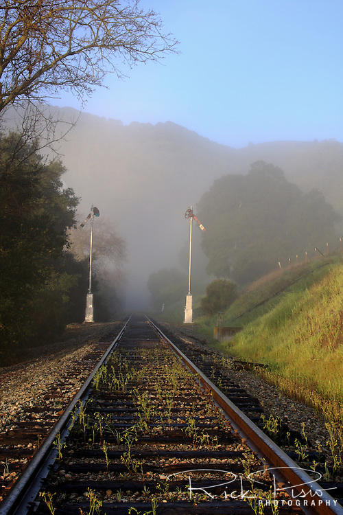 Railroad tracks and signal arms in the fog, Niles Canyon, California. Now operated by the Niles Canyon Railway the right away was first used by the Central Pacific Railway to complete the Transcontinental Railroad.