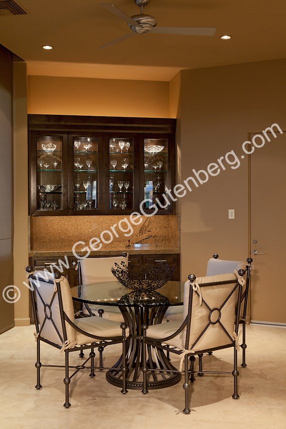 Small wrought iron and glass dining table is seen against glass cabinet stock photo of wine room