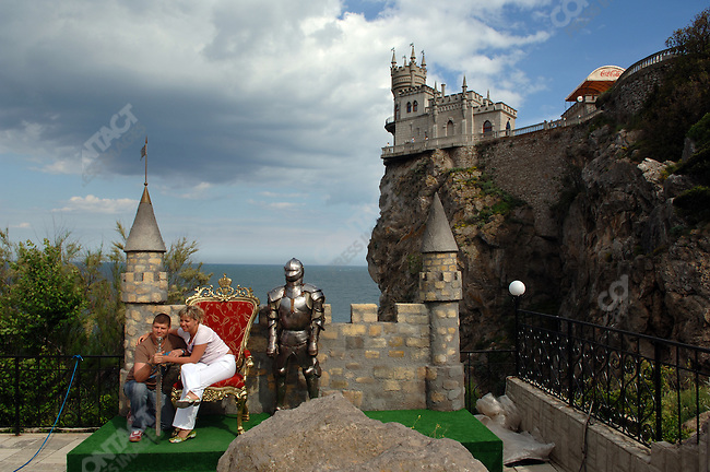 Tourists pose for a picture at the Swallow's Nest castle, located just outside of Yalta. Republic of Crimea, May 27, 2006.