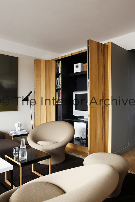 The sliding doors of the painted trompe l'oeil cupboards are partially open to reveal the bookcase and television