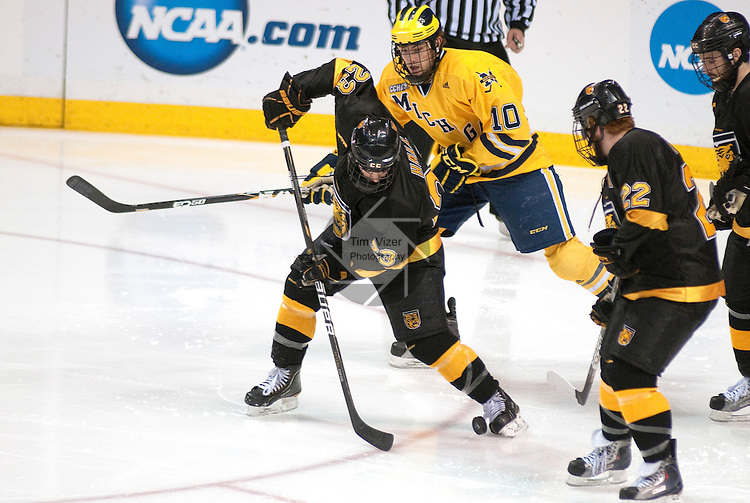 March 26,  2011                      Colorado left wing Tim Hall (23) tries to clear the puck away from his team's net area in the third period.  Behind him is Michigan forward Chris Brown (10) and at right is teammate, Colorado College center Nick Deneen (22). The University of Michigan defeated Colorado College 2-1 in the championship game of the NCAA Division 1 Men's West Regional Hockey Tournament, on Saturday March 26, 2011 at the Scottrade Center in downtown St. Louis.