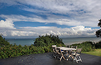 A garden table and chairs on a simple decking enjoy views over the coast