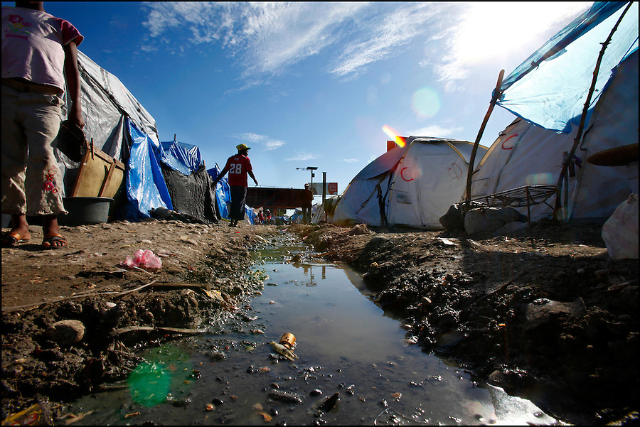Nov 11, 2010 - Port-au-Prince, Haiti.A stagnant drainage ditch filled with water, garbage and possible human waste runs through a tent city in Port-au-Prince, Haiti on Thursday, November 11, 2010 as fears of a Cholera outbreak spread through the area just days after cases of the infection were confirmed in Haiti's capital. Officials from the Pan American Health Organization warn that Haiti's cholera epidemic, spread primarily through consuming infected water and food, is likely to grow much larger in the wake of Hurricane Tomas.  (Credit Image: Brian Blanco)