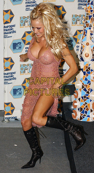 PAMELA ANDERSON.photo room at the MTV Europe Music Awards, Barcelona, Spain..November 14th, 2002.see through, see thru, transparent dress, knee high boots, cleavage full length pink black.CAP/PL.©Phil Loftus/Capital Pictures