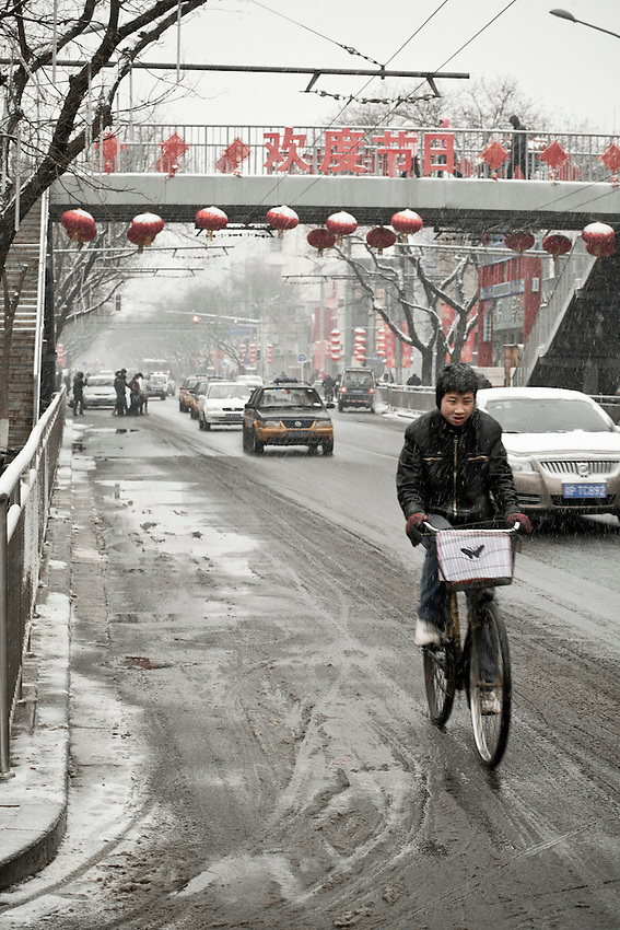 "A young chinese man cycling on the Dongsi avenue in the center of Beijing  after a snowfall that local authorities say they have artifically provoked to fight the exceptional drought in northern China. February 10 2011. On the bridge  the sentence say ""Welcome to the day of the festival"" , meaning the Spring festival (i.e the chinese new lunar year)just celebrated the february 3."