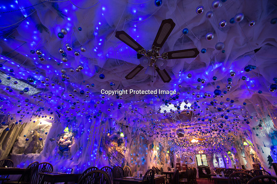 """30/11/15<br /> <br /> The 'Indoor Igloo'.<br /> <br /> It has taken a team of five, two weeks to put up this stunning display of Christmas decorations in what is believed to be one of Britain's most festive pubs. The race was on to put up the 7,500 baubles and 27,000 fairy lights, before guests arrived for the pub's first Christmas parties held last night. <br /> <br /> Each of the five rooms at the Hanging Gate at Chapel-en-le-Frith in the Derbyshire Peak District has a different theme or colour. This year the main restaurant is the Indoor Igloo, the bar area is purple and gold and there's the Candy Cain room upstairs in the pub near Buxton. There's also has another 10,000 lights on the outside of the building. <br /> <br /> """"We've had to replace a few thousand of the LED lights this year, I buy them in huge lengths so it's cost lots  to get everything ready"""" said landlord Mark Thomas.<br /> <br /> All Rights Reserved: F Stop Press Ltd. +44(0)1335 418365   www.fstoppress.com."""