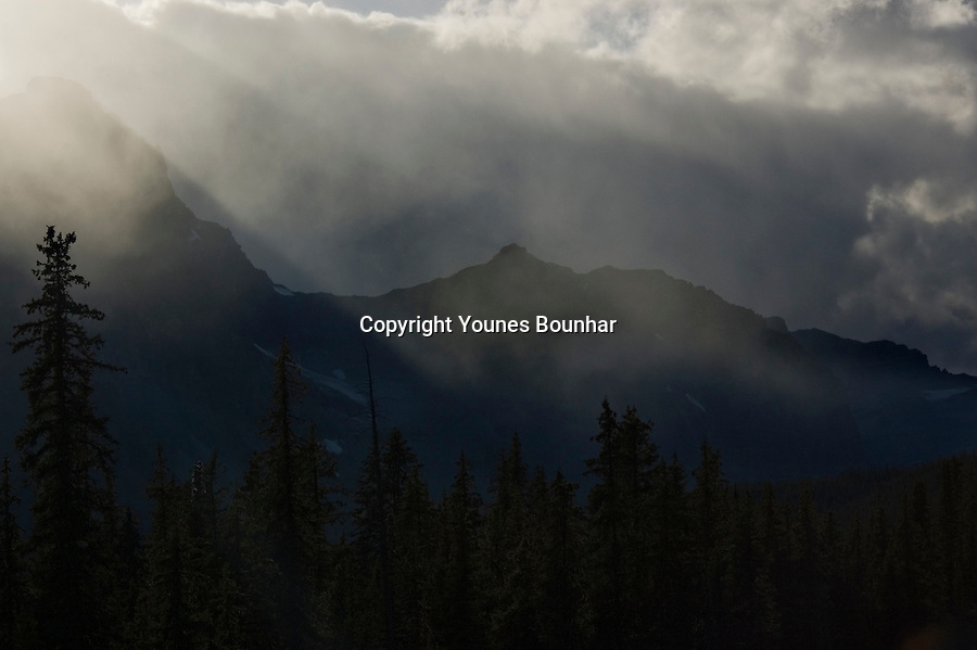 """God rays"", golden beams of light piercing through storm clouds over Crowfoot Glacier after rainfall"