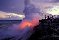 Tourists watching volcanic lava flowing into the sea at Hawaii Volcanoes National Park, Island of Hawaii