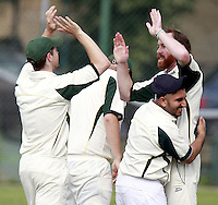 James Baker (R) of North London is mobbed after taking the wicket of James Russell during the Middlesex County Cricket League Division Three game between Highgate and North London at Park Road, Crouch End on Sat July 12, 2014