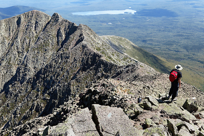 A hiker contemplates the view along the Knife Edge trail on Mt. Katahdin in Baxter State Park in North-central Maine.