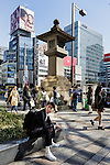 Tokyo, March 26 2015 - A fasionable young man waiting in front of the large traditional stone lantern that marks the way to Meiji Jingu Shrine from Omotesando Crossing at Aoyama Dori Avenue and Omotesando Avenue.