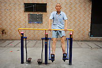 Pensioner exercising on a public exercise machine.