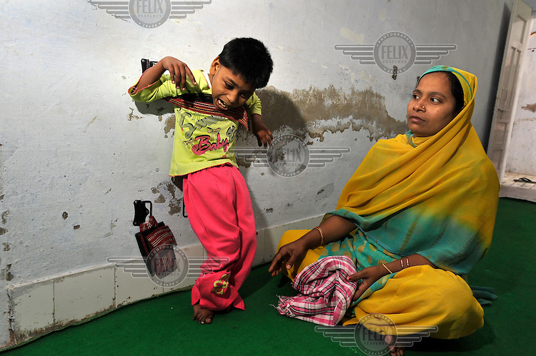 A mother with her child who has birth defects wait to be treated by a doctor at the privately funded Baba Farid Centre in Faridkot. An increasing and ignored percentage of children are being born suffering the side effects of industrial pollution. The Baba Farid Centre was set up by Dr Pritpal Singh and is staffed on a volunteer basis by his network of similarly concerned fellow junior doctors and specialists. It treats its patients with a mixture of homeopathic, ayurvedic and acupuncture methods.