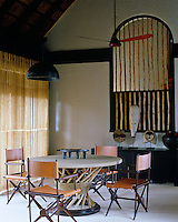 The double-height dining room is used during cooler winter evenings and is furnished with leather campaign chairs and a custom designed table by Andrzej Zarzycki