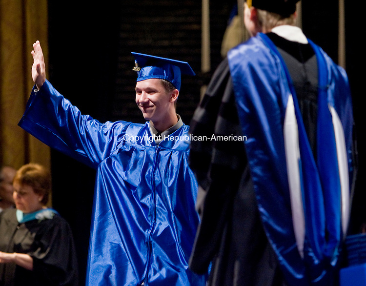 TORRINGTON, CT - 22 JUNE 2010 -062210JT06-<br /> Lewis Mills graduate Daniel Lipski waves to a cheering crowd as he  approaches Principal Dr. Karissa Niehoff during the presentation of diplomas during commencement ceremonies in Torrington on Tuesday.<br /> Josalee Thrift Republican-American