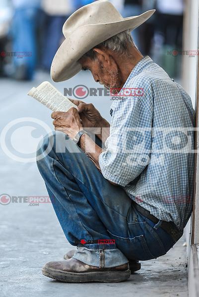 Un hombre viejo que viste de sombrero vaquero, lee un libro sentado la acera en el centro de hermosillo.<br /> Leer, lectura, libro, vaquero, anciano, old man,