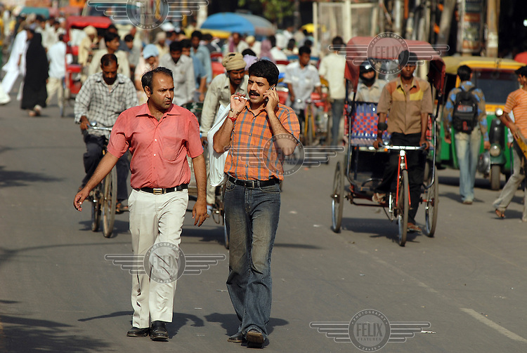 Middle class Indian men, one on a mobile phone, walking along one of the main streets/bazaars in the Old City area.