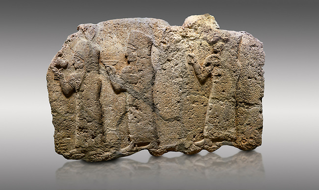 Picture & image of Hittite monumental relief sculpted orthostat stone panel of a Procession. Limestone, Karkamıs, (Kargamıs), Carchemish (Karkemish), 900 - 700 B.C. Anatolian Civilisations Museum, Ankara, Turkey.<br /> <br /> It is a depiction of three marching female figures in long dress with a high headdress (photos) at their head. These women are considered to be the nuns of the Goddess Kubaba. The figure in the front has a small animal in her right hand while the figure in the middle has a glass in his right hand. The object which the figures carry in their left is not understood.  <br /> <br /> Against a gray background.