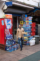 Essaouira, Morocco.  Customer Leaving Small Grocery and Sundries Shop with Bread for the Day.   Bottled Water Supplies around the Entrance.