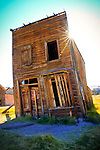 California, East Central, Bodie, Lee Vining. SUn peaks over a rustic building in the historic Ghost town of Bodie.