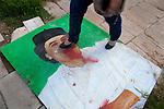 A woman walks across a defaced portrait of Col. Muammar Gaddafi lies on the ground in Misrata, Libya, Oct. 6, 2011. In the wake of its success in repelling the long siege of Misrata by Qaddafi loyalists, the Misrata military council has not been afraid of asserting its authority.