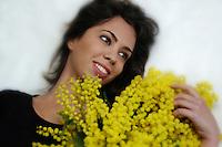 Donna con la mimosa, simbolo della festa della donna. Woman with Mimosa, Acacia dealbata, symbol of celebration of women. ...