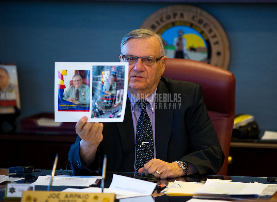 Jan 21, 2015; Phoenix, AZ, USA; Maricopa County sheriff Joe Arpaio holds up a photo showing a banner of him currently on display in Times Square in his office in downtown Phoenix. Mandatory Credit: Mark J. Rebilas-