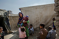 KABUL, AFGHANISTAN - SEPTEMBER 22: <br /> A woman walks back to her home with  her child as she leaves an outreach clinic with supplies for her malnourished child at the Chamane Babrak IDP camp on September 22, 2013 in Kabul, Afghanistan.