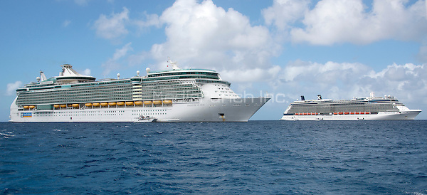 Two large cruise ships, from left to right, the Royal Caribbean Freedom of the Seas, which carries 4,515 passengers and 1,360 crew, and the Celebrity Reflection, which carries 3,609 passengers and 1271 crew, in the harbor of George Town, Grand Cayman in the Cayman Islands on Tuesday, December 20, 2016.  The smaller boats are tenders to ferry passengers back and forth to the island. Both Royal Caribbean and Celebrity are brands of Royal Caribbean International.<br /> Credit: Ron Sachs / CNP /MediaPunch