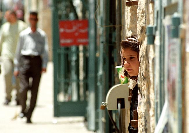 Strassenszene in Betlehem<br /> Immer wieder wird die palaestinensische Stadt Betlehem von der israelischen Armee belagert. Zum Teil tagelang duerfen die Bewohner ihre Haeuser nicht verlassen. Etliche Bewohner verloren bei den Kaempfen im April/Mai 2002 Angehoerige. Es gebe keine Familie in der heiligen Stadt, die nicht einen Toten zu beklagen habe, erzaehlen die Menschen. In den Tagen ohne israelische Soldaten, erweckt die Stadt einen normalen Anschein. Die Menschen gehen ihrem taeglichen Leben nach. Allerdings sind Touristen in diesen Tagen in der heiligen Stadt nicht zu sehen. Die Strassen sind so gut wie leer, die Wirtschaft liegt brach.<br /> Hier: Ein Maedchen beobachtet in der Altstadt die Strasse.<br /> 19.05.2002, Betlehem<br /> Copyright: Christian-Ditsch.de<br /> [Inhaltsveraendernde Manipulation des Fotos nur nach ausdruecklicher Genehmigung des Fotografen. Vereinbarungen ueber Abtretung von Persoenlichkeitsrechten/Model Release der abgebildeten Person/Personen liegen nicht vor. NO MODEL RELEASE! Nur fuer Redaktionelle Zwecke. Don't publish without copyright Christian-Ditsch.de, Veroeffentlichung nur mit Fotografennennung, sowie gegen Honorar, MwSt. und Beleg. Konto: I N G - D i B a, IBAN DE58500105175400192269, BIC INGDDEFFXXX, Kontakt: post@christian-ditsch.de<br /> Bei der Bearbeitung der Dateiinformationen darf die Urheberkennzeichnung in den EXIF- und  IPTC-Daten nicht entfernt werden, diese sind in digitalen Medien nach &sect;95c UrhG rechtlich geschuetzt. Der Urhebervermerk wird gemaess &sect;13 UrhG verlangt.]