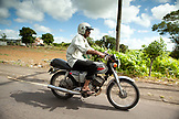 MAURITIUS, a man drives his moped through a rural town