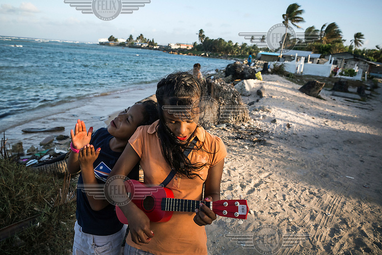 Children playing an ukulele on the beach during a low tide on the eroded coastline at Jenrok village, which is slowly being destroyed by the rising seas.