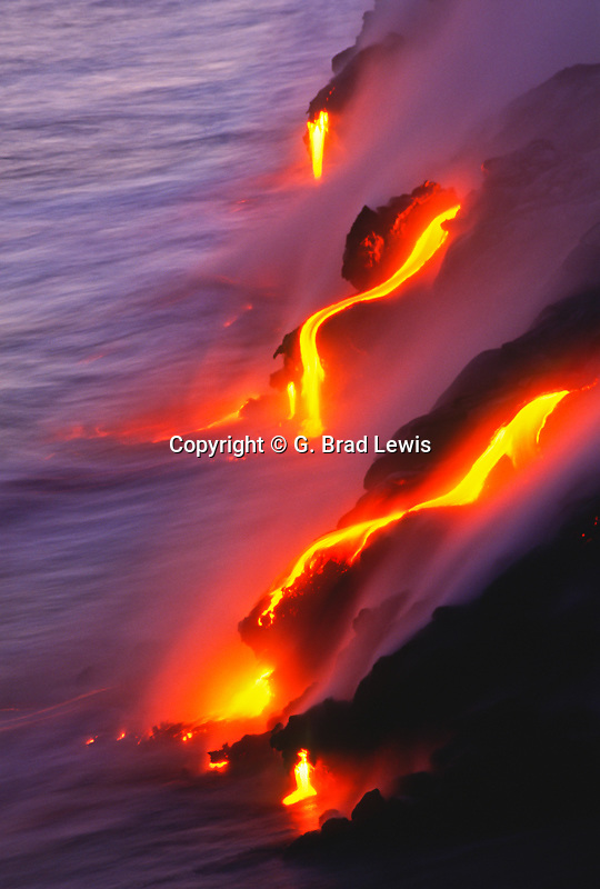 Bright colored lava falls into the Pacific Ocean at dusk releasing vapour