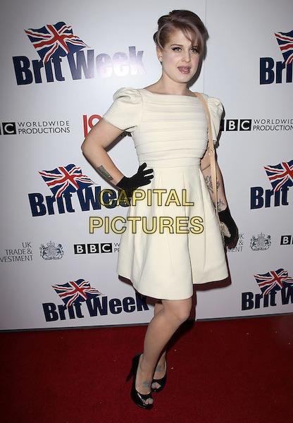 KELLY OSBOURNE .The BritWeek 2010 Champagne Launch held At The British General Consul Residence, Los Angeles, California, USA..April 20th, 2010.full length white cream dress hand on hip black gloves open toe shoes tattoos bag purse   .CAP/ADM/KB.©Kevan Brooks/AdMedia/Capital Pictures.