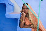 Rajasthani girl in traditional clothes sitting on steps in front of blue house in Blue City (old town); the blue houses were originally for Brahmins but non-Brahmins soon joined in, as the colour was said to deflect the heat and keep mosquitoes away, Jodphur, Rajasthan, India --- Model Released