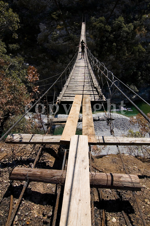 Simple suspension bridge with two people above the river Tara, Montenegro, Europe